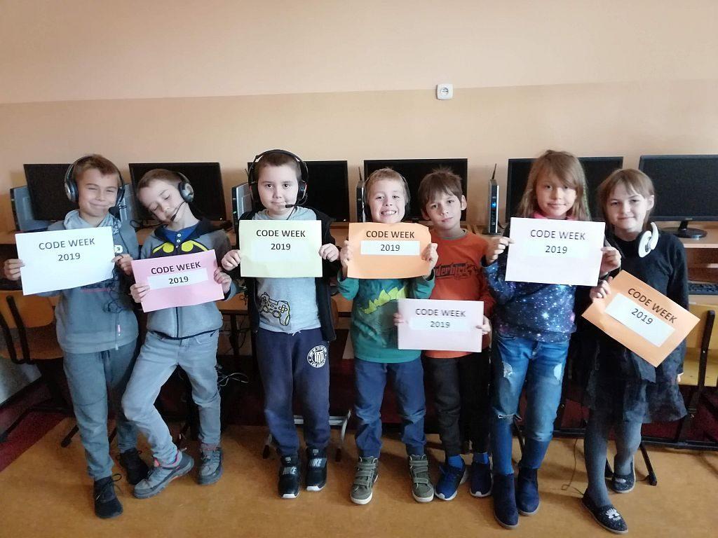 Dzieci pozujące i trzymające kartki z napisem Code Week 2019