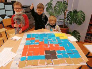 Dzieci przy stole z matą do kodowania