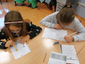 Dziewczynki wykonujące zadania przy stole
